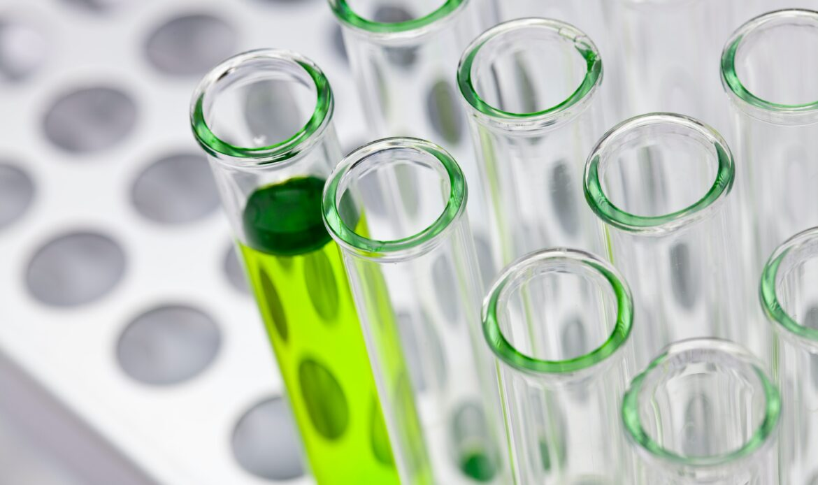 Close up of test tubes with green liquid in one of them.