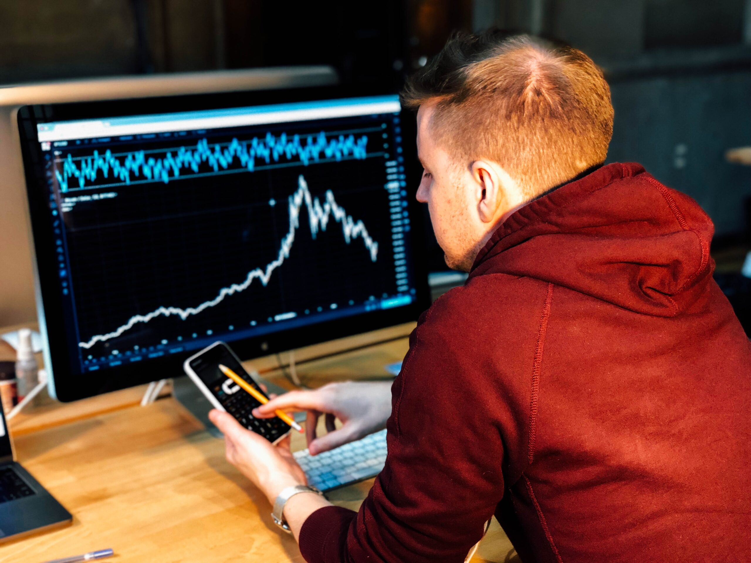 Man working on financial analyzing on a computer and phone.