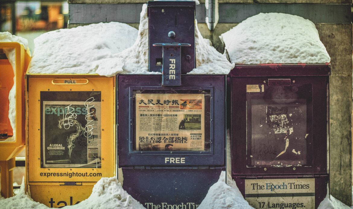 Three newspaper stands covered in snow.