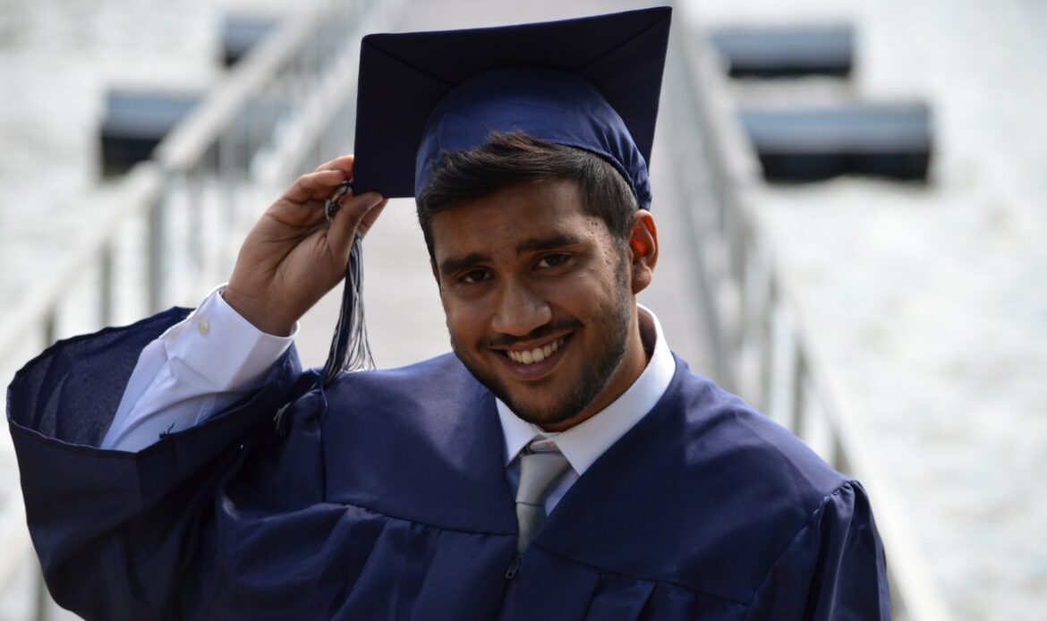 A man in a blue graduation cap and gown, tipping his cap.