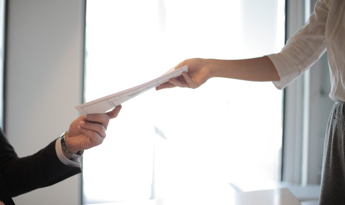 A woman handing her resume off to another person.