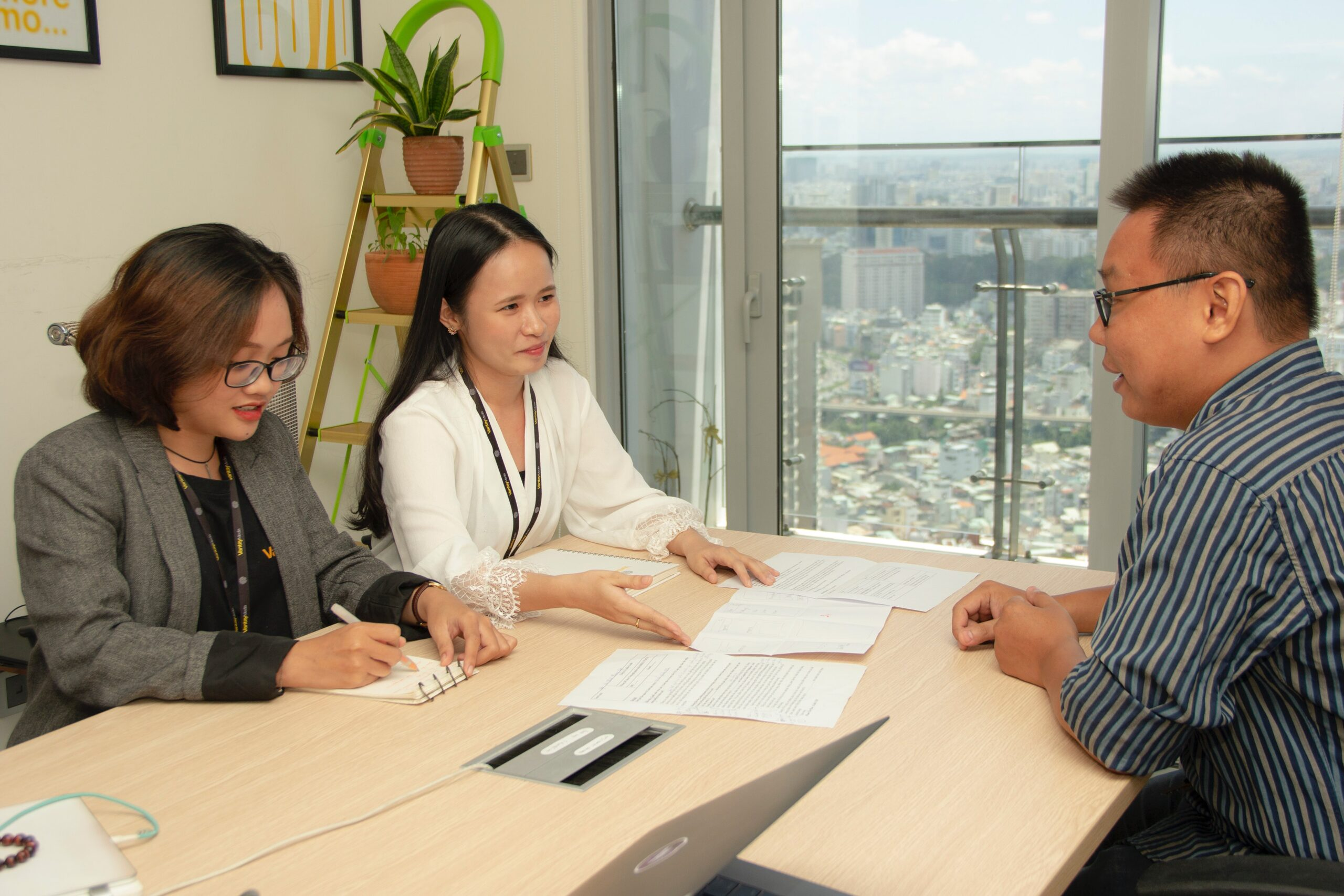 Two women and a man sitting on opposite ends of a table, in the interview process