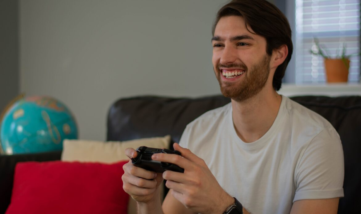 Man sitting on a couch with a video game controller in his hand