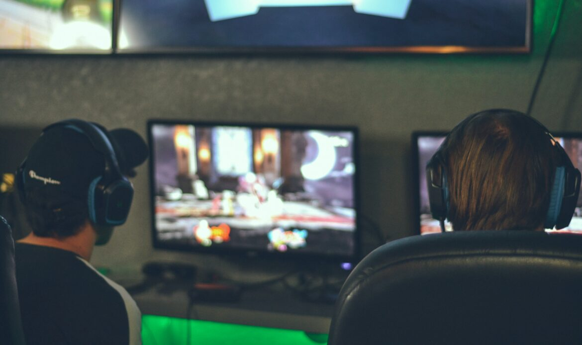 Two men facing computer screens with gaming headsets on their heads.