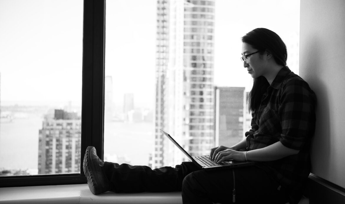 Woman sitting at the window, typing on a laptop.
