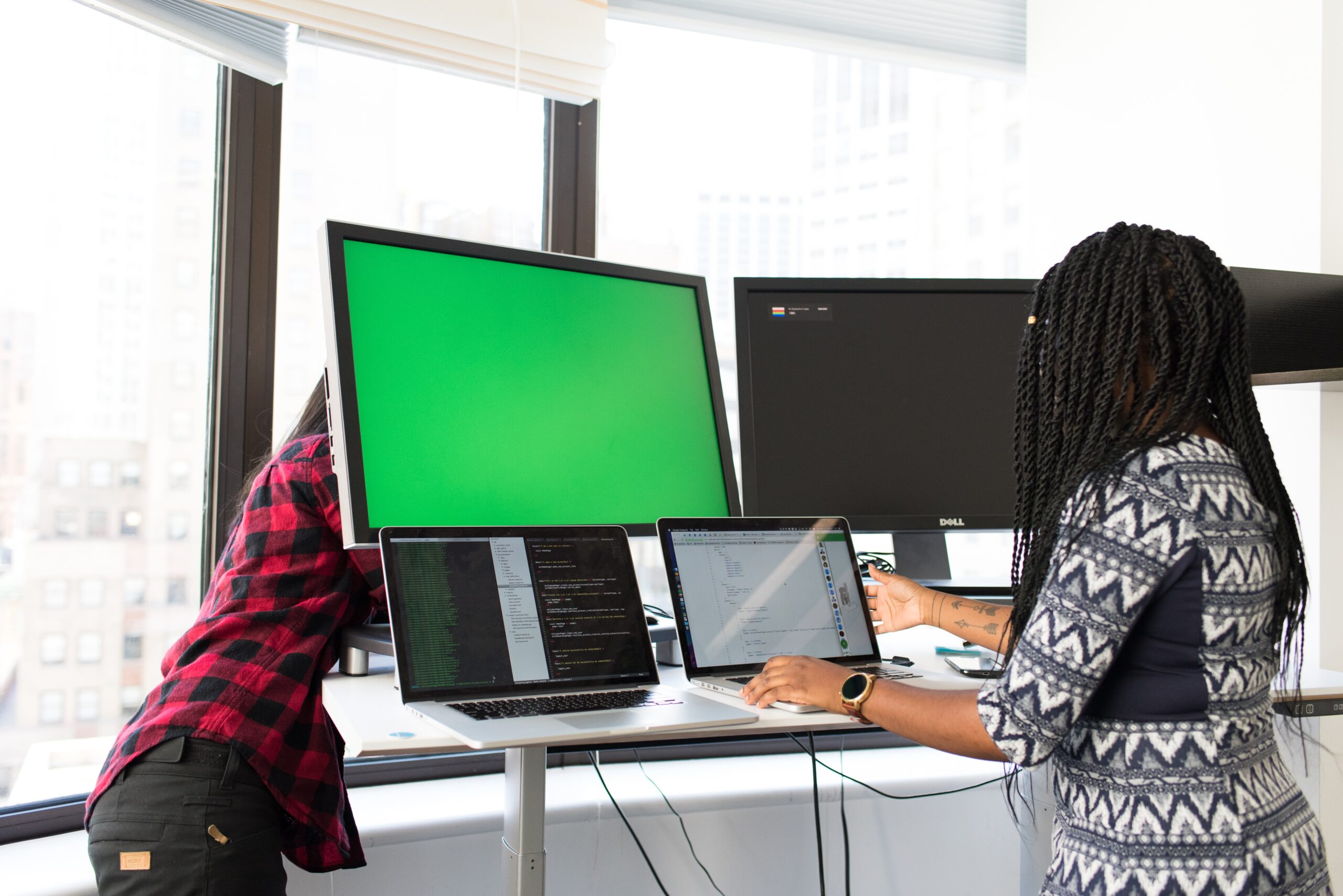 A woman working at a standing desk at two monitors