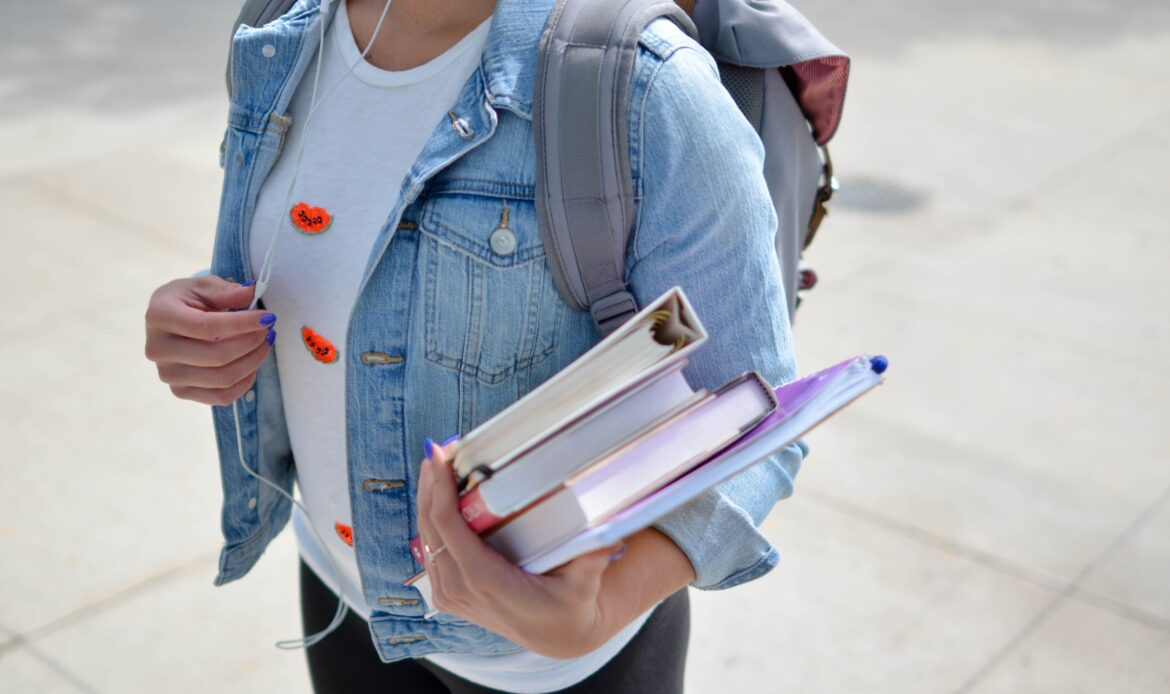 Person walking on a sidewalk with a backpack and a stack of books.