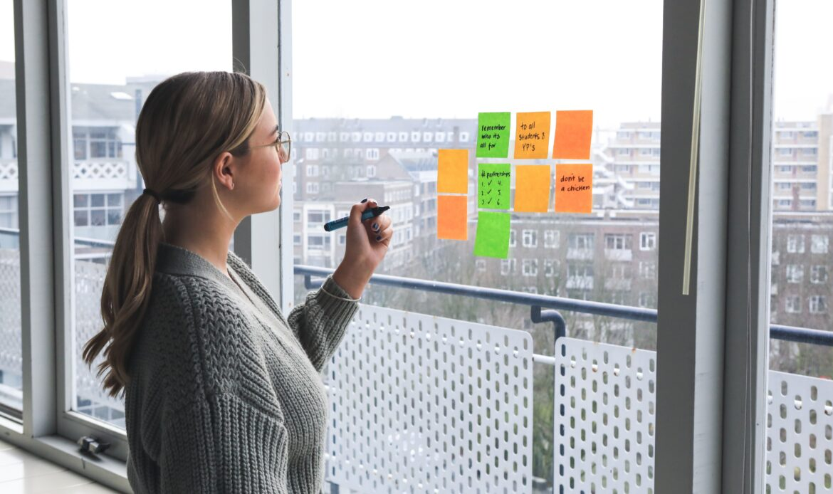 Woman writing post-it notes that are stuck to a window.