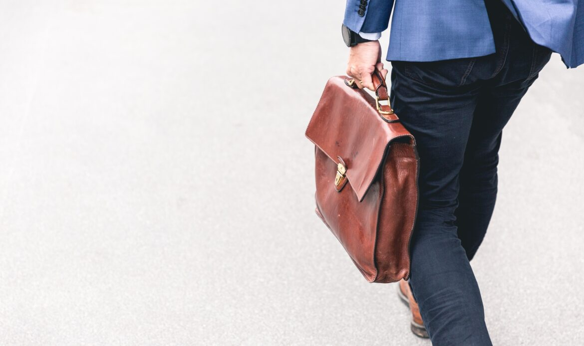 Man wearing a suit walking into work with a briefcase