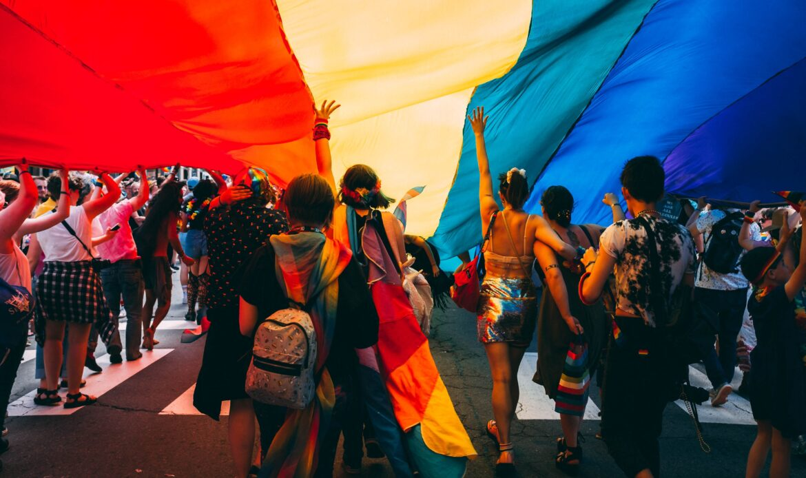 People celebrating at a gay pride underneath a rainbow flag.