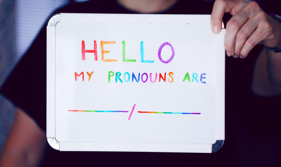 """A person holding up a whiteboard that reads """"HELLO MY PRONOUNS ARE"""" in rainbow letters."""