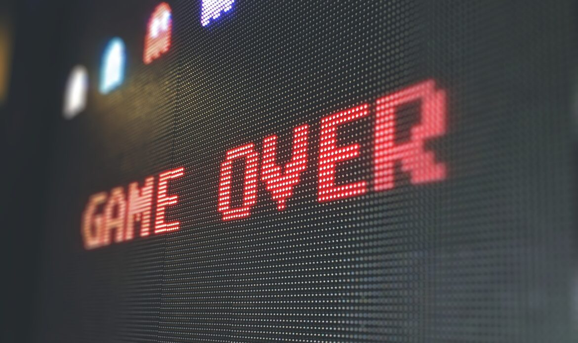 """An electronic screen with the text """"GAME OVER"""" in red block lettering"""