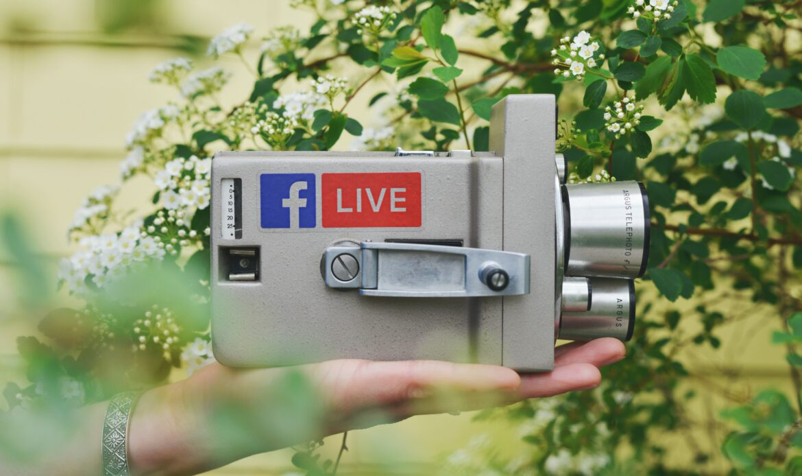 A hand holding a camera with a Facebook and Live sticker on it.