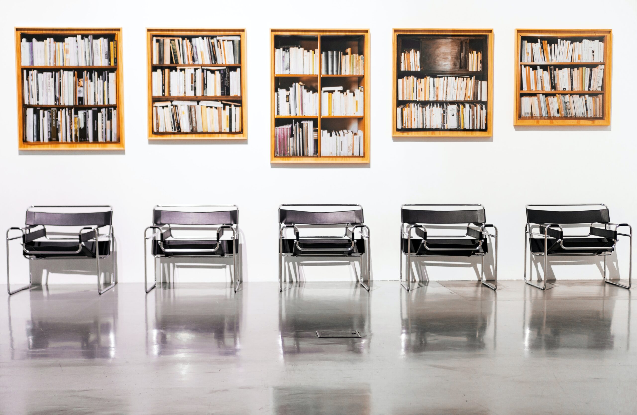 Four chairs lined up with bookshelves above each of them.