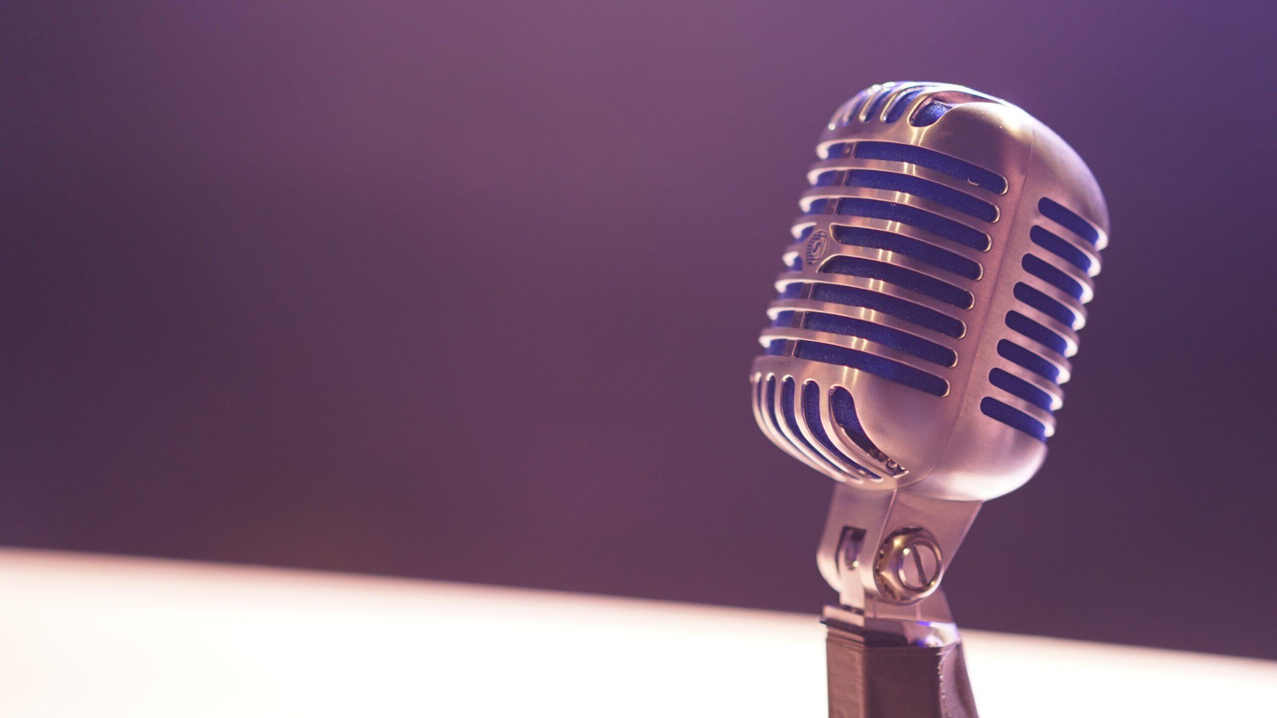 A dark room with a spotlight on an older microphone