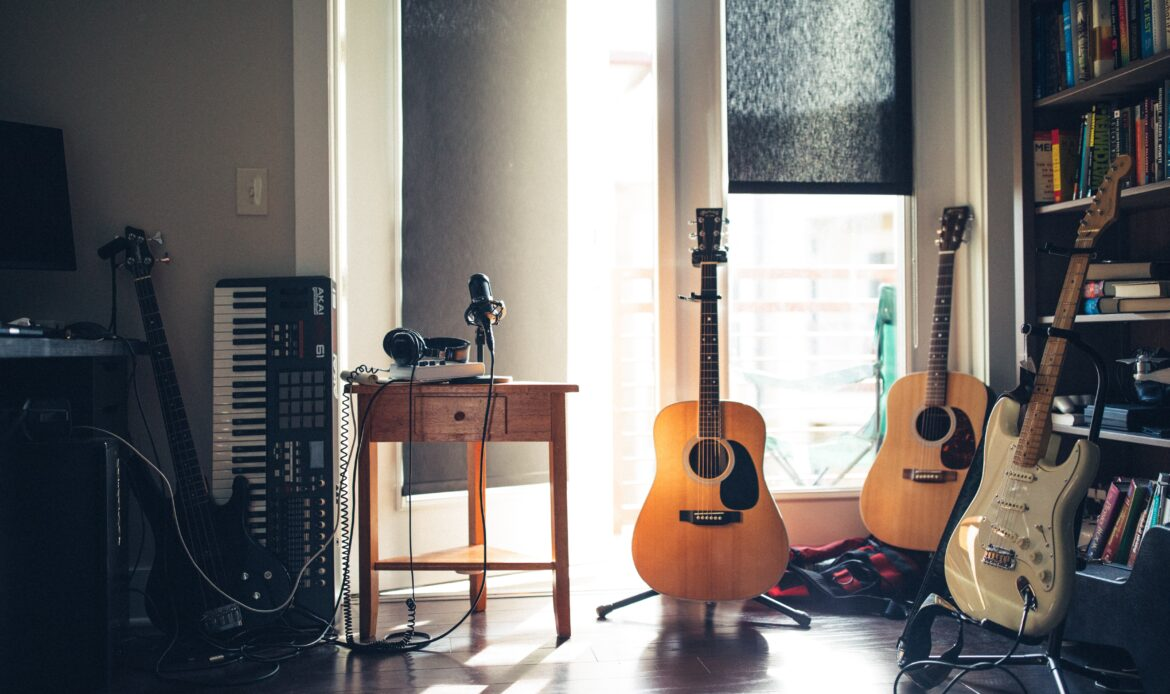 Two guitars, a keyboard, and microphone in a room that is backlit