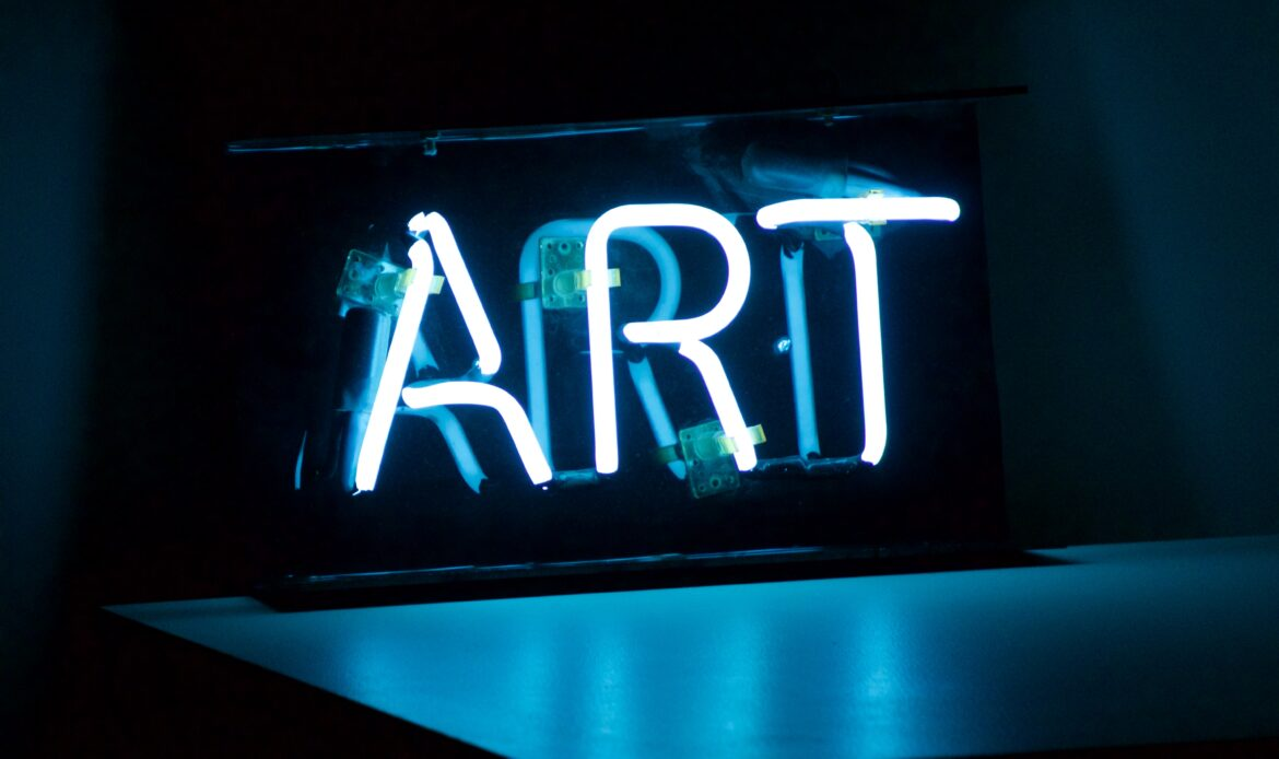 """A white neon sign that reads """"ART"""""""