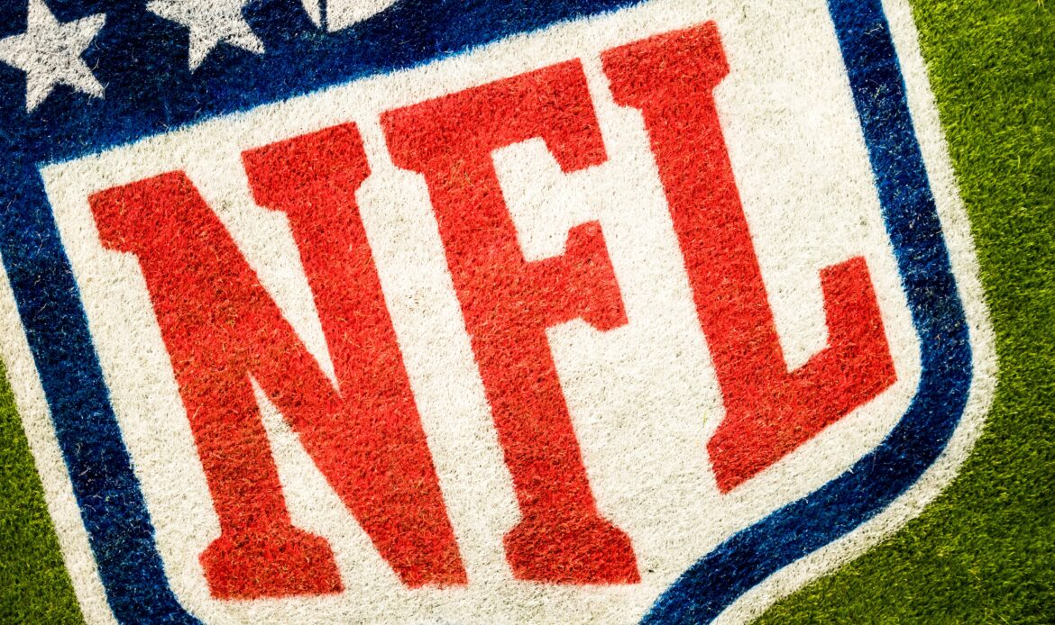 A close up of turf spray painted with the NFL logo.