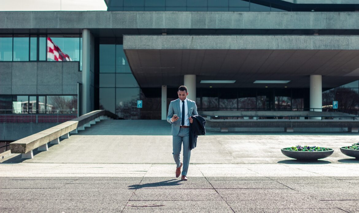 Man wearing a suit walking out of a building, looking down at his cellphone.