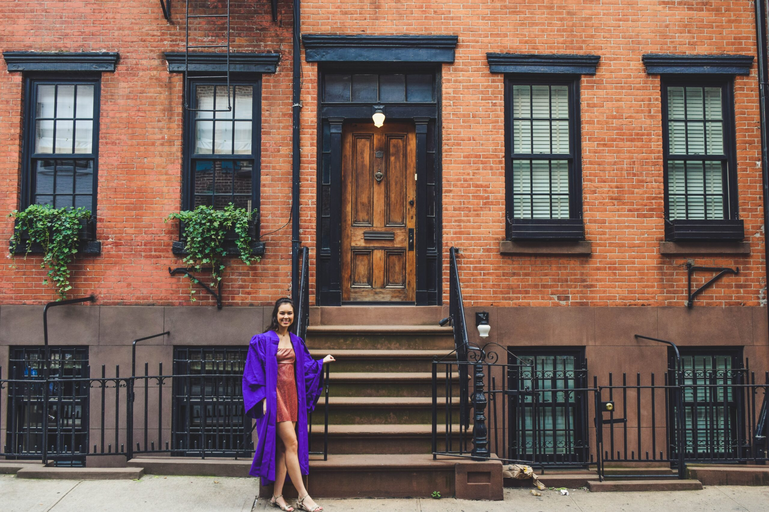 NYU student in graduation gown, outside of an apartment complex