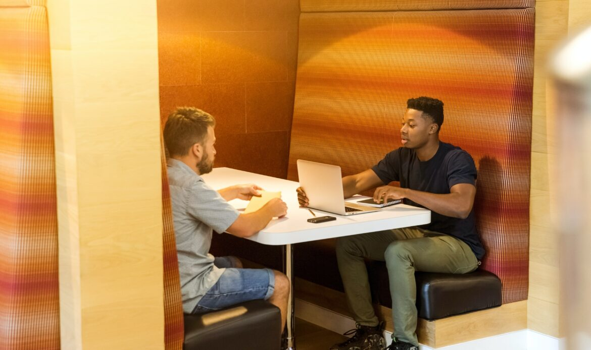 Two men working together at a booth. One has a laptop open and the other has a notebook.