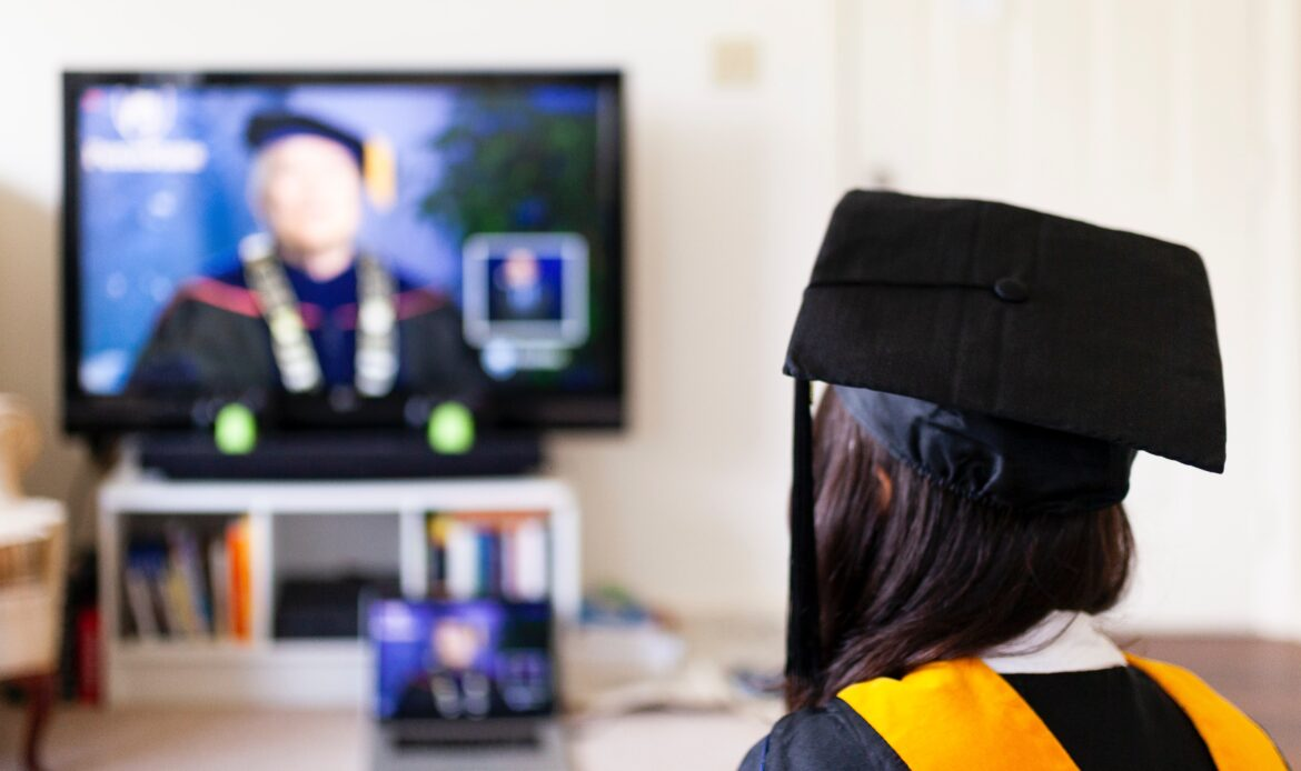 Woman sitting in her living room, watching a virtual graduation with her cap and gown on.