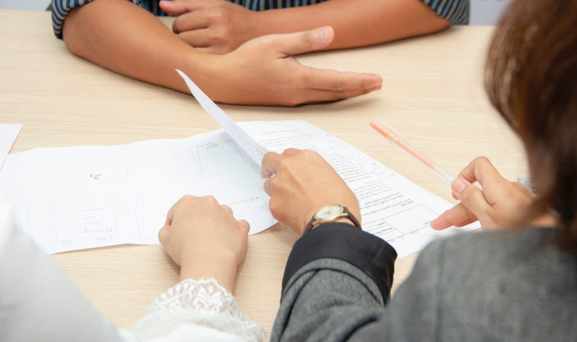 Two people interviewing someone, a close up of the hands, handing over paper.