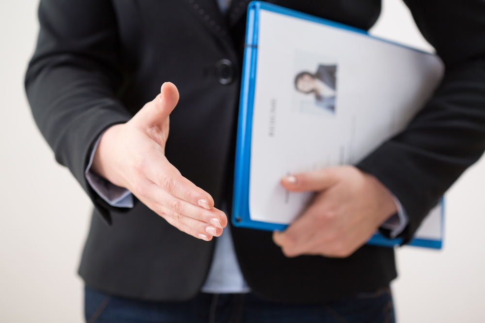 Man outreaching his hand to shake hands, holding a folder with a resume