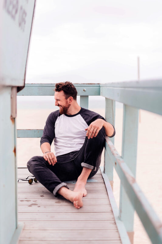 A Picture Of A Happy Man Sitting Down On A Deck