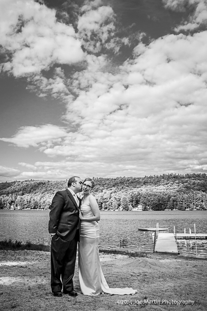 A groom kissing his new bride on the cheek in this B&W fine art portrait.