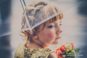 Flower girl sits under an umbrella at this wedding in New Hampshire