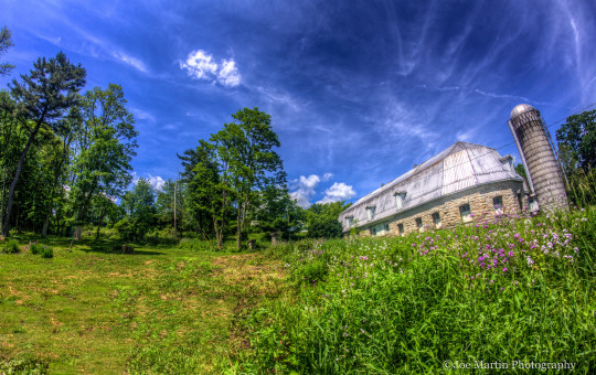 Fine art photo of a Wide shot of a barn the field next to it and the beautiful sky in this