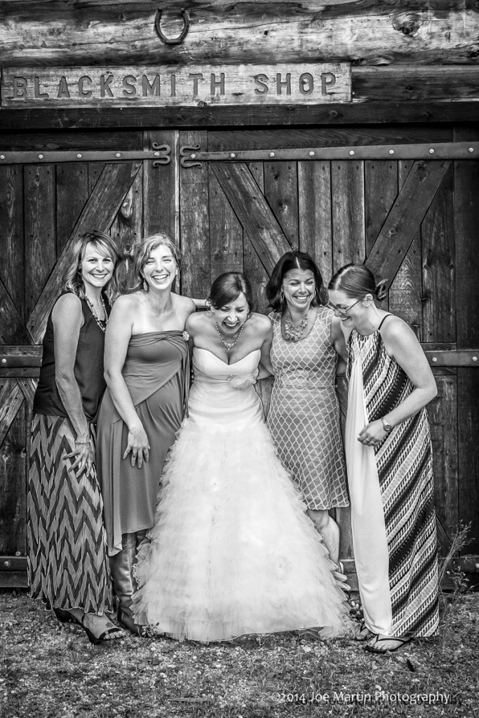 Wedding photo of the bride with some girl friends laughing. Posed in front of a New England barn
