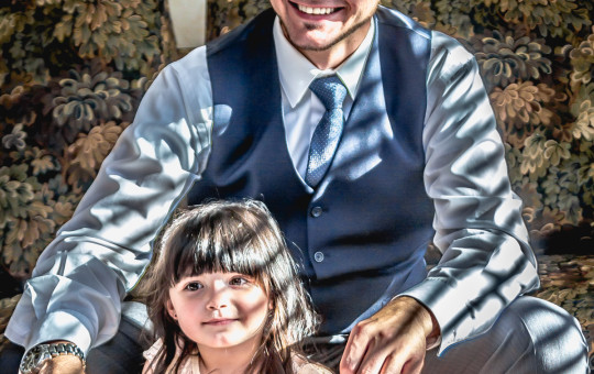 Photo of a groom and his little girl before the wedding sitting coloring together.