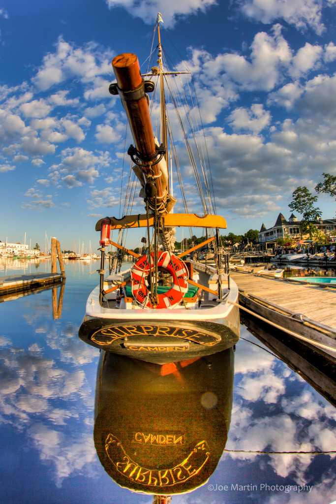 Image of a boat with an amazing reflection and clouds.