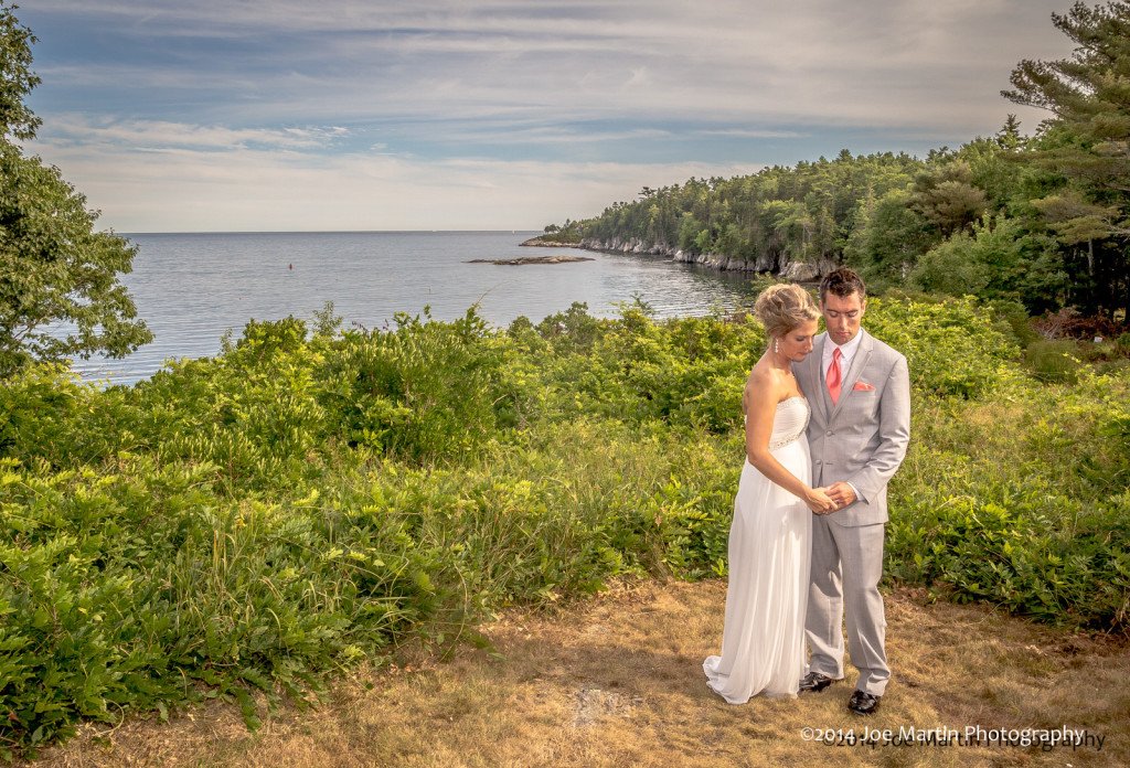 Bride and groom look at their rings in this sea side wedding photo