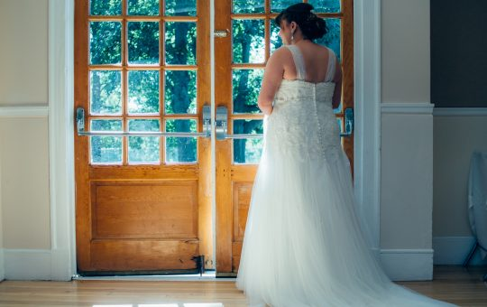 Soon to be bride looking out windows at her wedding guests