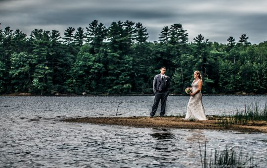 Wedding photo with a couple posed near a Maine Lake