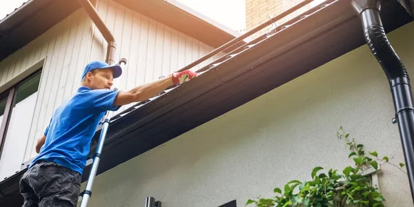 man performing roof and gutter inspections