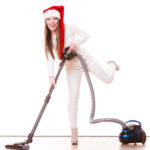 A young woman in a Santa hat cleans floors before the holidays