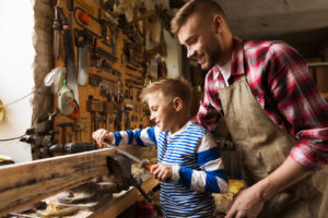 A father helps his son with using a hand tool before placing it in hand and power tool storage unit