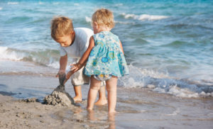 Two kids enjoy playing in the sand on a Cape May beach