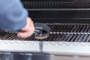 A man cleans grill grates before storing a gas grill for winter
