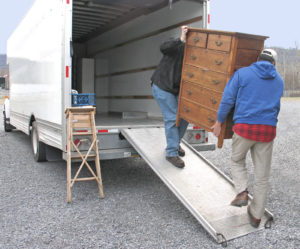 Two people moving items into a moving truck