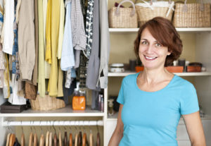 A woman standing in front of her organized closet