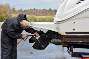 A man cleans his boat with a pressure washer