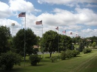 Flag poles fly the American flag at Centennial Park