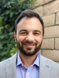 Headshot of male therapist with beard smiling outside