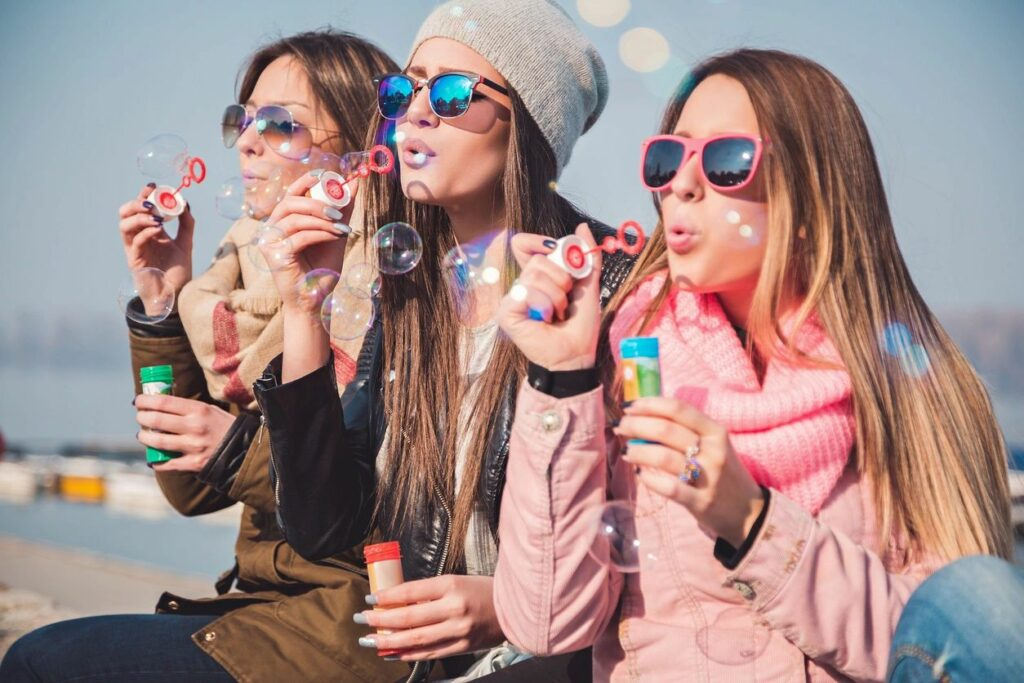 women blowing bubbles together