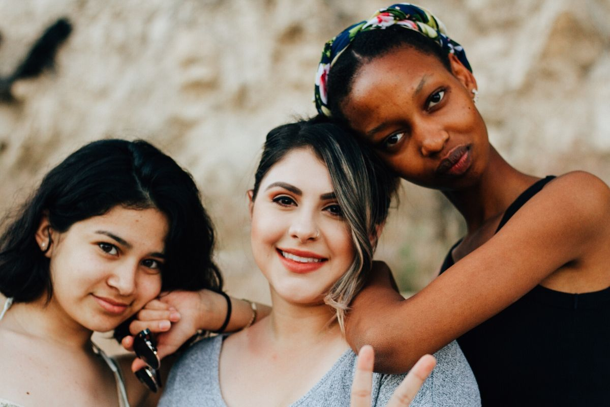 Three women with different skin types pose for a picture.